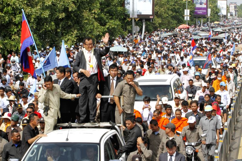Sam Rainsy, president of the opposition Cambodia National Rescue Party (CNRP), greets supporters in front of Phnom Penh International Airport in Phnom Penh, ...