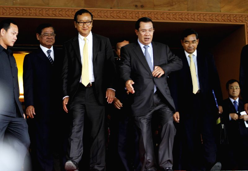 Cambodian Prime Minister Hun Sen (R front) and Sam Rainsy, president of the opposition Cambodia National Rescue Party, exit from a meeting room in Phnom Penh, ... - Hun Sen