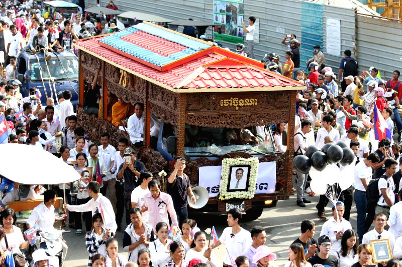 PHNOM PENH, July 24, 2016 - People attend the funeral procession of a slain Cambodian political analyst in Phnom Penh, Cambodia, July 24, 2016. Tens of thousands of mourners on Sunday attended the ...