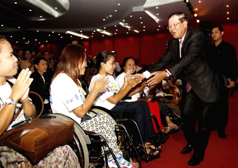Cambodian Prime Minister Hun Sen (2nd R) greets disabled people in Phnom Penh, Cambodia, July 3, 2014. Hun Sen on Thursday launched a five-year national ...