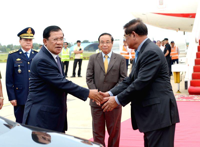Cambodian Prime Minister Hun Sen (L, front) arrives in Phnom Penh, Cambodia, June 18, 2014. Cambodian Prime Minister Hun Sen was not sick during his landmark ...