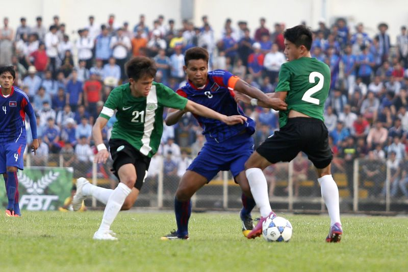 Cambodian players (in blue) and Macao players vie for the ball during the preliminary qualifying round match in Phnom Penh, Cambodia, March 12, 2015. Cambodia's ...