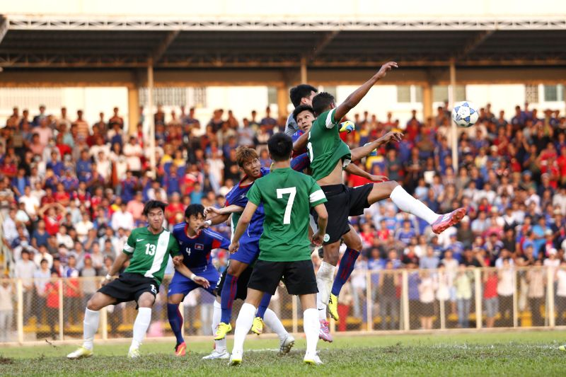 Cambodian players (in blue) and Macao players (in dark green) vie for the ball during the preliminary qualifying round match in Phnom Penh, Cambodia, March 12, ...