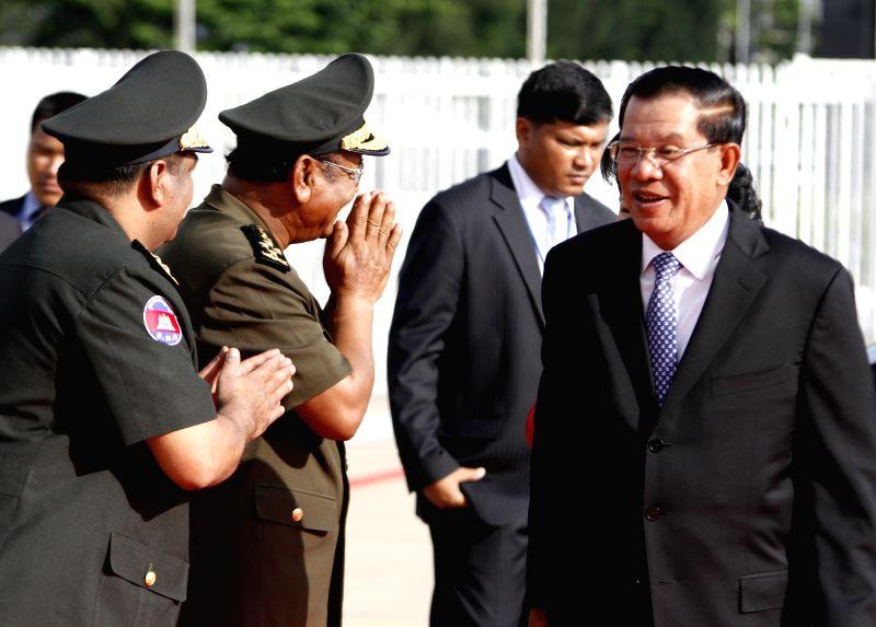 Cambodian Prime Minister Hun Sen (1st R) appears at Phnom Penh International Airport in Phnom Penh, Cambodia, May 18, 2014. Hun Sen left for Shanghai, China on ...