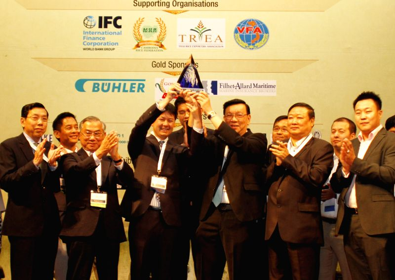 Phnom Penh: Sok Puthyvuth (4th L), president of the Cambodia Rice Federation and Chookiat Ophaswongse (5th R), honorary president of the Thai Rice Exporters Association, raise the world's best rice ..