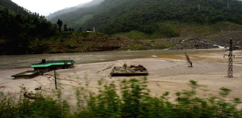 Photo taken on Aug. 2, 2015 shows the remains of houses trapped in a dam formed in Sunkoshi River after the massive landslide occurred a year ago on Aug. 2, ... - Sunil Sharma
