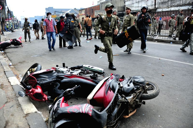 Photo taken on Aug. 20, 2015 shows motorcycle laying on the ground after a clash which occured during a demolition of illegal settlements at the Kampung Pulo ...
