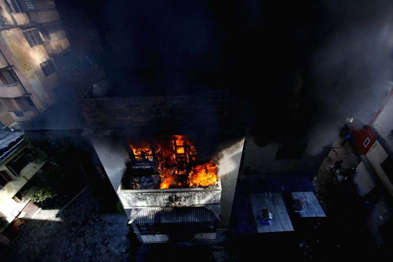 Photo taken on Dec. 9, 2015 shows houses that caught fire due to electric short circuit at an electronic wholesale house in Basantapur, Kathmandu, Nepal. The fire ...