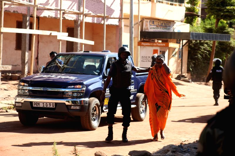 Photo taken on Nov. 20, 2015 shows a freed hostage leaves with the help of the police in Bamako, Mali. At least 80 people taken hostage by unidentified gunmen in ...