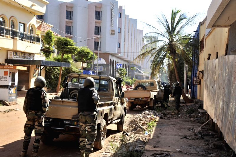 Photo taken on Nov. 20, 2015 shows Malian soldiers cordoning off streets near Radisson Hotel in Bamako, Mali. At least 80 people taken hostage by unidentified gunmen ...