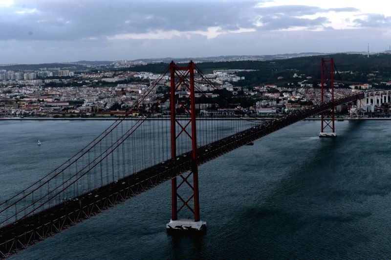 Photo taken on Nov. 21, 2015 shows 25 de Abril Bridge (25th of April Bridge) connecting Lisbon to Almada across the Tejo River, in Lisbon, capital of Portugal. ...