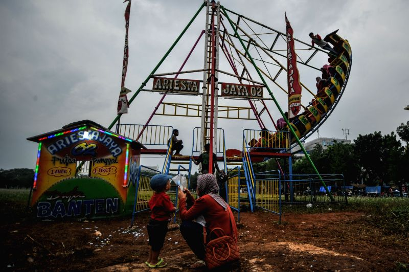 Photo taken on Nov. 24, 2015 shows a mother and her child at the carousel field in Tangerang, Indonesia. Travelling entertainment group, or travelling carousel ...