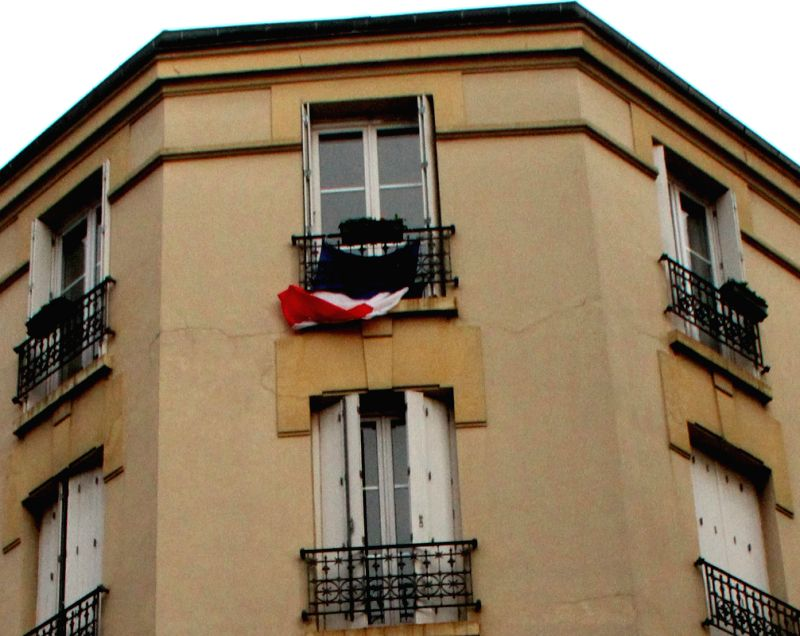Photo taken on November 27, 2015 shows a French national flag outside a building window during the National Tribute to the victims in the November 13 Paris attacks in ...