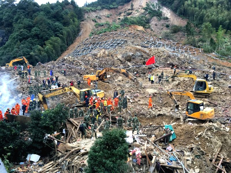 Photo taken with a mobile phone shows rescuers working at the accident site after a landslide hit Lidong Village of Yaxi Township in the outlying Liandu District of ...