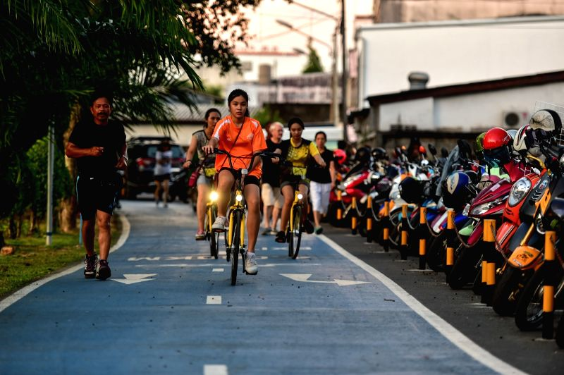 PHUKET, Oct. 7, 2017 - Local residents ride ofo sharing-bikes on a bike lane at a public park in Phuket, Thailand, Oct. 5, 2017. China's dock-less bike-sharing company ofo provided more than 1,000 ...
