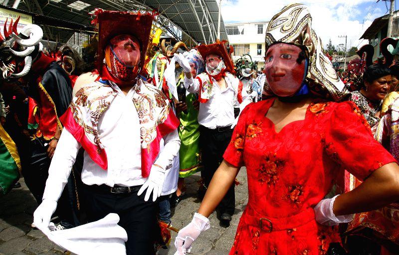 """A couple wearing masks take part in the traditional parade """"Diablada de Pillaro"""", in Pillaro, central highlands in Ecuador, on Jan. 2, 2015. Diablada is a ."""