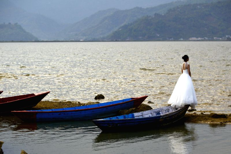 A bride from China poses for a photo in Pokhara, Nepal, April 10, 2015.