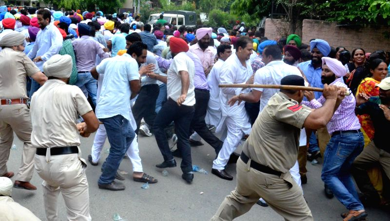 Police charges lathis on the members of Elementary Teachers Training Union who were staging a demonstration in Amritsar on Aug 3, 2014.