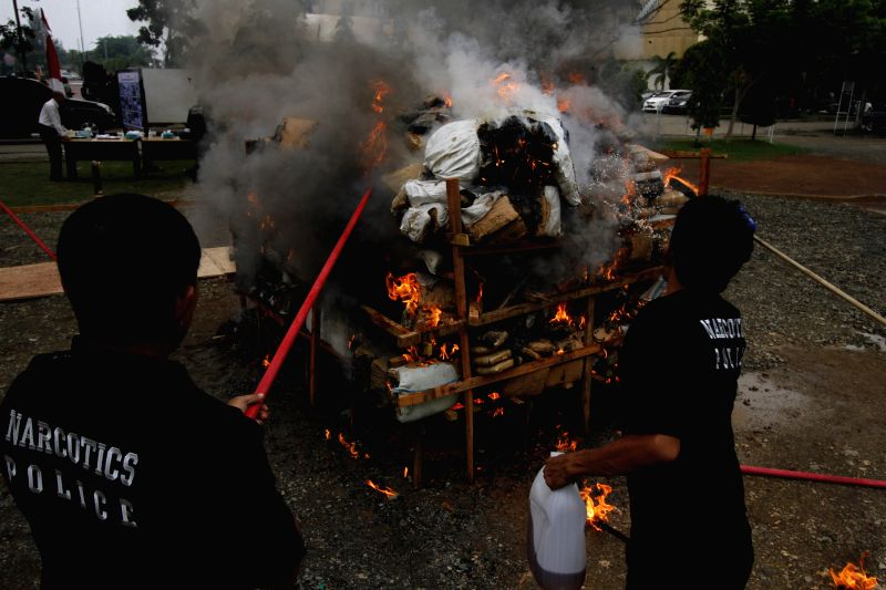 Police officers burn down confiscated drugs in Banda Aceh, Indonesia, Oct. 29, 2015. Indoensian narcotics police torched more than two tons of dry cannabis during the ...