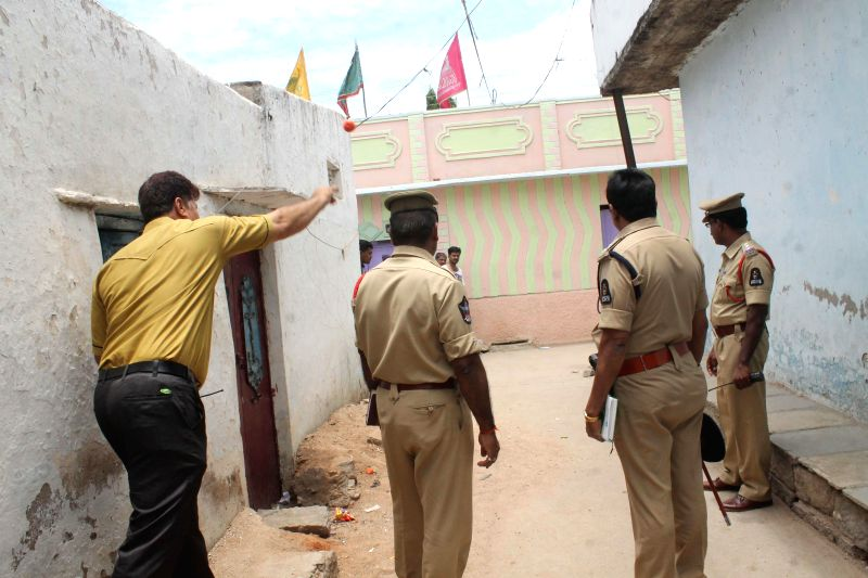 Police officials inspect the site where a low-intensity bomb exploded on 6th May, 2014 at Bhavani Nagar slum area of Talabkatta in Hyderabad on May 7, 2014.