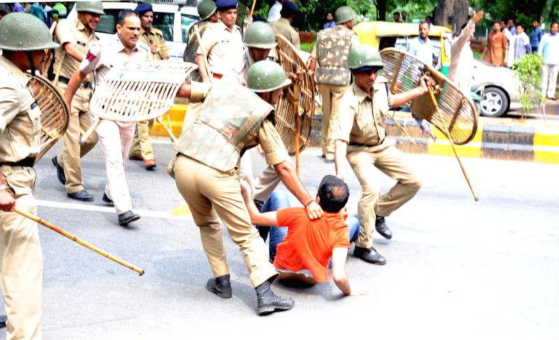 Police personnel arrest an ABVP activist demonstrating outside UPSC office in New Delhi on July 14, 2014.