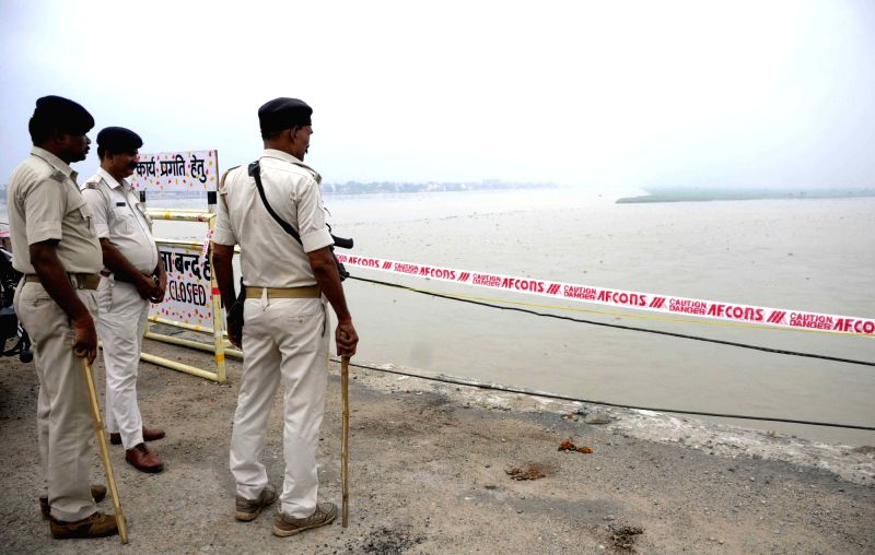 Police personnel at the site where rescue operations are underway after a car fell into Ganga river, in Patna on July 31, 2018.