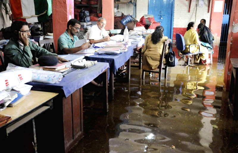 Police personnel at work in flooded Kadamkuan Police station of Patna on Aug 18, 2014.