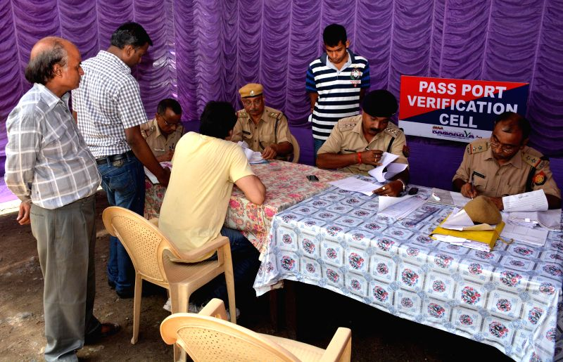 Police personnel busy working as applicants wait in the newly opened Passport Verification Cell at Pan Bazar police station in Guwahati on July 25, 2014.