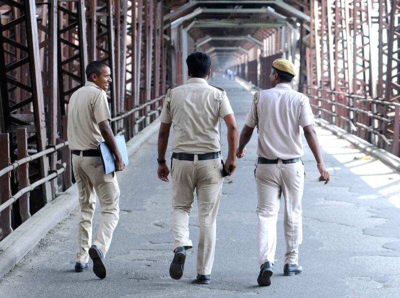 Police personnel carry out surveillance at the old Yamuna rail bridge that was closed for train traffic since Sunday night as a precautionary measure after the river crossed the ...