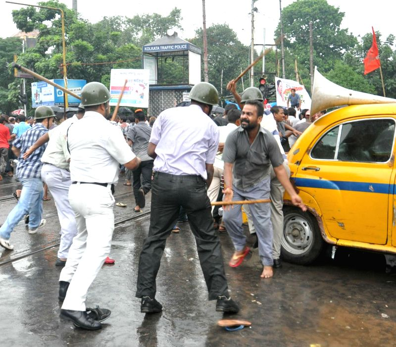 Police personnel charge lathis on taxi drivers demonstrating against police atrocities in Kolkata on Aug 7, 2014.