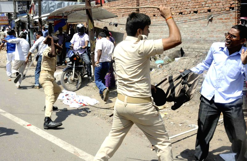 Police personnel charge lathis on teachers in Patna on July 15, 2014.