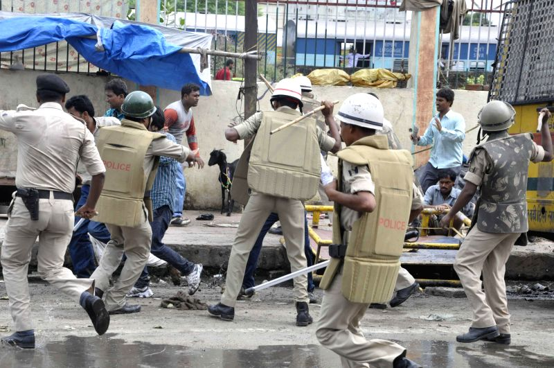 Police personnel charge lathis on the members of Sankhyaki Syawam Sewak Sangh in Patna on July 1, 2014.