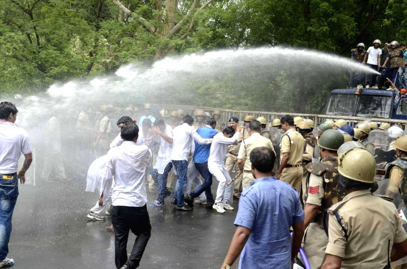 Police personnel charge water cannon on NSUI activists demonstrating against MPPEB scam in Bhopal on July 18, 2014.