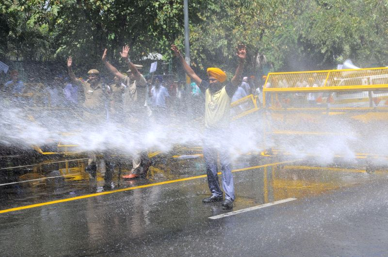 Police personnel charge water cannons on the members of the Delhi Sikh Gurudwara Prabandak Committee and Siromoni Akali Dal workers demonstrating against  in front of the residence of Congress ... - Amarinder Singh