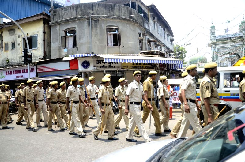 Police personnel conduct a flag march in Mahim ahead of 2014 Lok Sabha Elections in Mumbai on April 21, 2014.