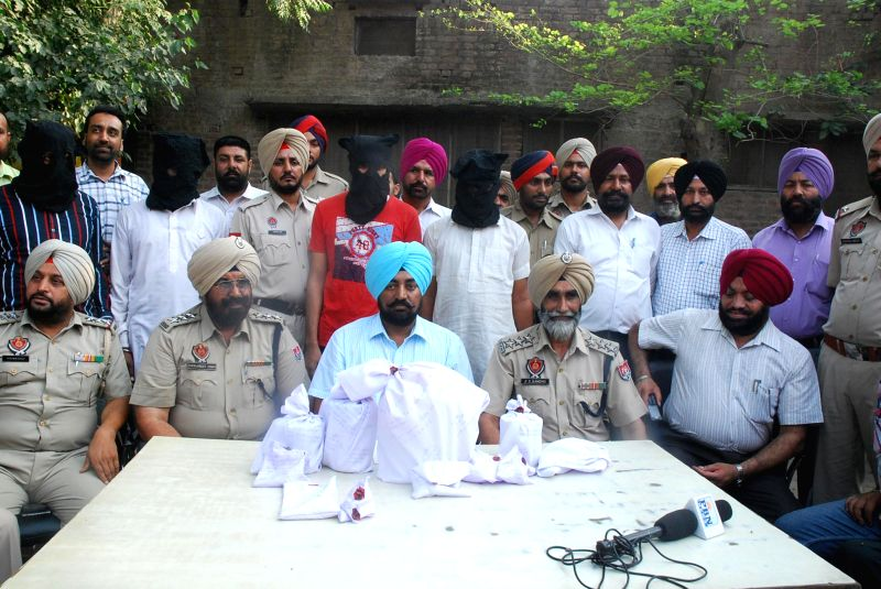 Police personnel display 4 kg heroin, a pistol and 500 gram opium recovered from drug peddlers at Sarai Amanat Khan in Tarn Taran of Punjab on  May 8, 2014. - Sarai Amanat Khan