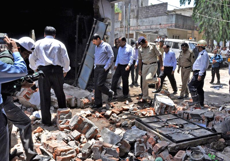 Police personnel inspect the site where a gas cylinder exploded in a godown at Pandesara of Surat on May 12, 2014. Reportedly 32 people were injured in the accident.