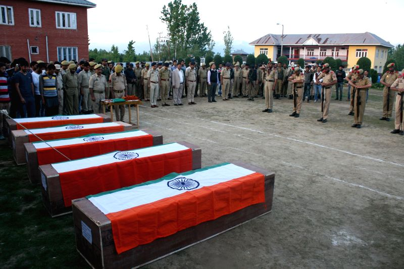 Police personnel pay tribute to the five martyrs who were shot dead by militants in Jammu and Kashmir's Kulgam district on May 1, 2017. Terrorists shot dead five policemen and two bank ...