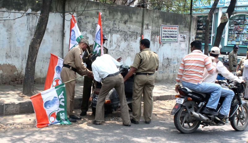 Police personnel remove flags of a political party from a scooter in Hyderabad on April 14, 2014.