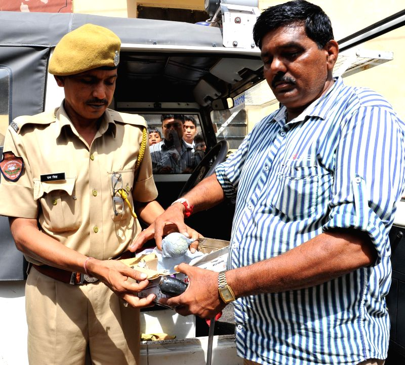 Police personnel show a crude bomb recovered from Purani Basti area of Jaipur on Aug 19, 2014.