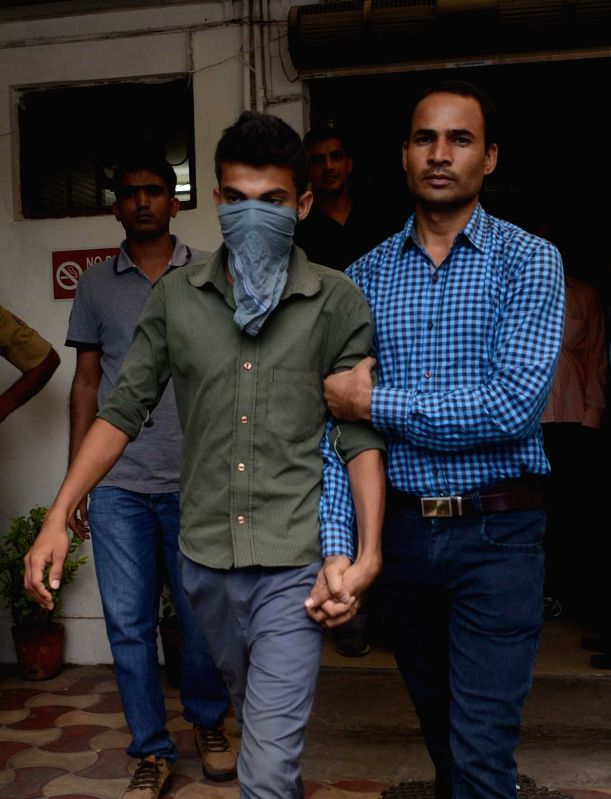 Police personnel take a person who along with four others is accused of stabbing a 19-year-old youth to death in broad daylight, for hearing at a Delhi Court on Aug 7, 2014.