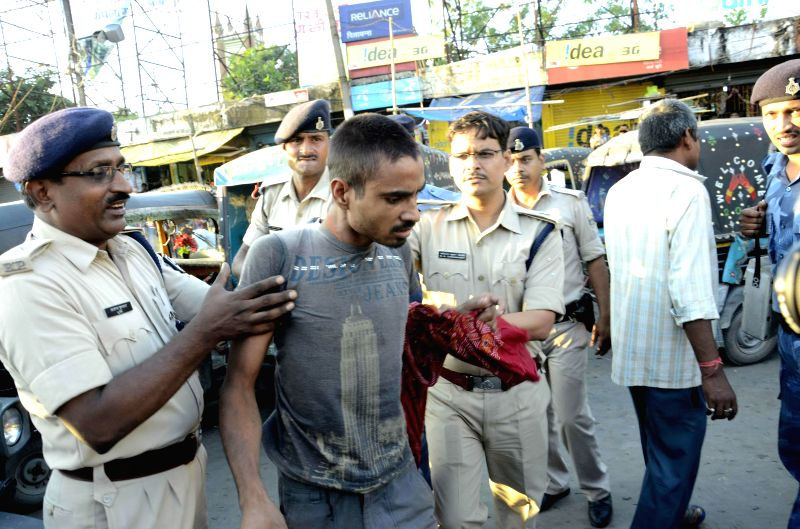 Police personnel take away auto-rickshaw drivers staging a road block in Patna on Sept 1, 2014.