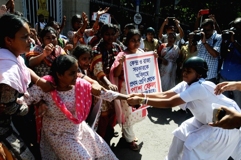 Police personnel take away Socialist Unity Centre of India (Communist) activists staging a demonstration, in Kolkata, on July 19, 2018.