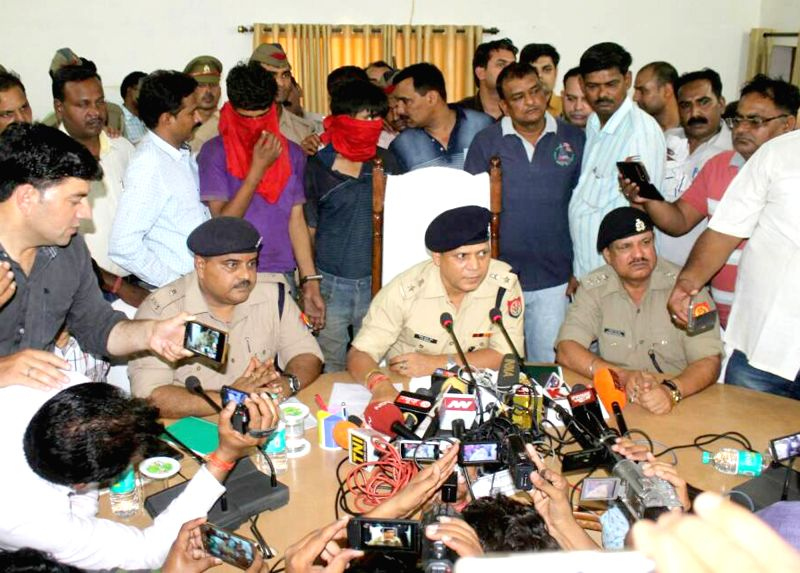 Police present before press two persons arrested in connection with murder of two bullion traders, in Mathura on May 20, 2017.