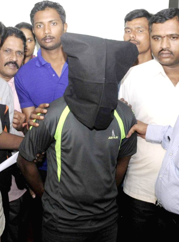 Police produces skating instructor of a private school who is accused of raping a 6-year-old student of the school, before media after arresting him in Bangalore on July 21, 2014.