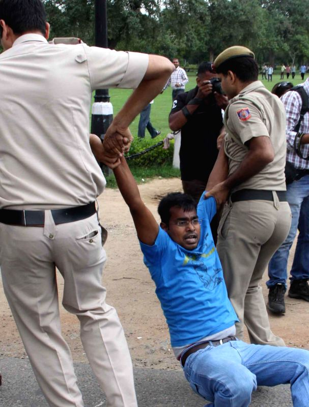 Police take away civil service aspirants demonstrating near Parliament to press for scrapping of Civil Services Aptitude Tests (C-SAT) in New Delhi on July 25, 2014.