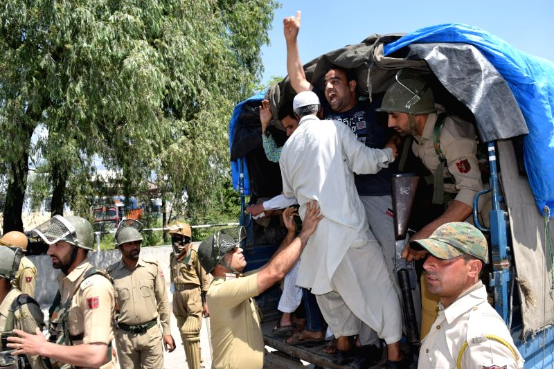 Police take away Hurriyat Conference activists as they take part in a protest march on the death anniversaries of Mirwaiz Molvi Farooq and Abdul Gani Lone in Srinagar on May 21, 2016.