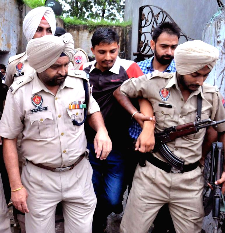 Police take away Mukesh Chaudhary in custody from Khurla Kingra area of Jalandhar on July 26, 2016. Chaudhary is aide of an army personal Rajiv Ranjan who had fled  after attacking his ... - Mukesh Chaudhary