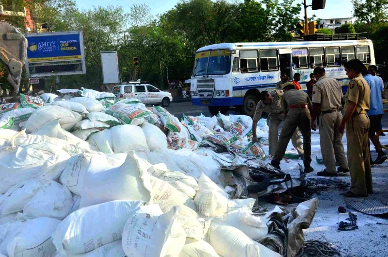 Policemen at the site where five persons, including three women, were killed when a speeding truck swerved and fell on their car along with its over 400 tonnes of salt in Jaipur on June 6, ...