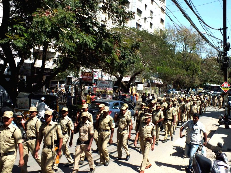 Policemen conduct flag march in Hyderabad's Masab Tank area after family members of car mechanic Syed Sharfuddin who was killed by the rowdy sheeters staged protest along with the dead ...